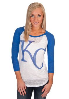 """You'll look great for the next Royals game in this Kansas City Royals Womens Royal Blue & White Jr. Fit Raglan Burnout T-Shirt! This Blue and White Ladies KC Royals 3/4 Sleeve Tee features a scoop neck with royal blue sleeves and neckline trim and a white body with classic """"KC"""" logo across the chest."""
