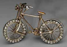 Bicycle brooch by Streeter & Co., probably English, c. 1896, of gold, enamel, old brilliant-cut diamonds and ruby