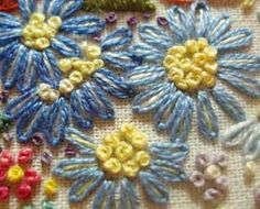 Embroidered Flower Gardens: Daisies    Continuing on with some examples of flowers in hand embroidery, here are a few simple daisy-like flowers with French knot centers.