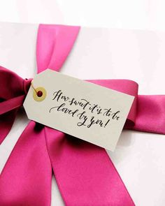 A letterpressed tag and a bow of fuchsia ribbon sealed the striped box of welcome goodies.