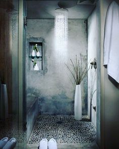 Beautiful shower. Ciment and cobble stone. Shower directly from roof save the walls.