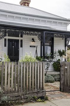 wooden fence and salvaged metal gate, porch metalwork trim and planters: