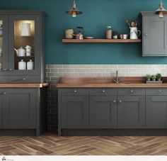 A modern classic shaker kitchen is influenced by the Victorian trend. The dark grey in frame shaker door has been given a free standing look, with classic solid oak worktops. The warm oak herringbone flooring and open shelf brings warmth to the sea green walls. Hints of copper contrast against the dark tones in this classic kitchen design.