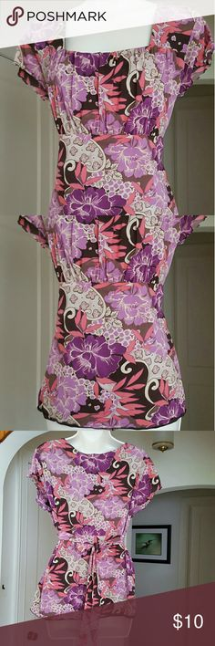 Tie-Back Empire Short-Sleeve Blouse Coral, lilac, purple, tan and brown flowers and leaves swirl diagonally across this lined figure-flattering top. It ties just under the bust. The ties can be doubled if you don't want a bow in back. I purchased it at Macy's or Nordstrom. There is no size/brand tag on it because it was too itchy. I wore this when I was a size 16/18. If you're not too busty, it should be okay if you're a 20. It's my favorite summer top, but I'm a 22/24 now, so someone else…