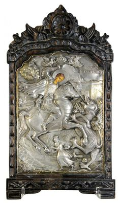 Greek icon, depicting St.George the Dragon Slayer . The reponsse decorated oklad ( hallmarked .950 ),and having gilt accents centered in a wood frame with floral carved medallion.: Lot 2024