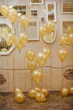Bexigas douradas cheias com gás hélio e amarradas com fitas também podem compor um lindo cenário! Eu adoro! Imagem: Pinterest