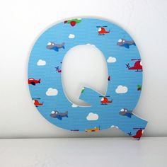 Letras Decorativas infantiles Q con aviones y nubes de estilo infantil en la parte frontal. Letra decorativa de material con acabado similar a letras de madera