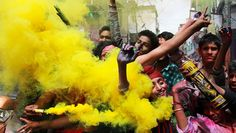 Menschen werfen auf der Straße buntes Pulver und bunten Rauch in die Luft. Happy Holi aus Indien.