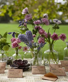 """... lovely arrangements ... used here on a seating cards table, a casual grouping of posies. Place stems like viburnums, double tulips, hyacinths, """"Tote"""" lilies, clematises, lisianthus, umbrella ferns, anemones, gomphrenas, muscari, and succulents in assorted glass bottles for a fresh-from-the-garden look."""