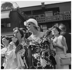 U.K. Women attending the All England Lawn Tennis, London, 1960 // by Bob Collins. Well-dressed women attending the All England Lawn Tennis and Croquet Club Championships at Wimbledon are photographed looking up towards scoreboards in unison
