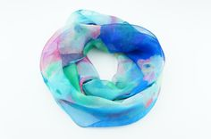 A very light blue green SILK chiffon loop scarf has a pattern of light blue green pink water flowers is a great choice for a romantic evening or day wear. The size allows a double wrap and gives warm hug because of natural textile. Lightweight, reversible infinity scarf, neck accessory. Be playful, feminine and elegant!  Material: silk Dimensions: Width: 19 / 49 cm Length (circle): 52 / 132 cm  Care instructions: (silk, chiffon, cotton, polyester) Warm hand wash with mild detergent...