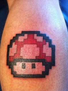 A tattoo of the 1980s magic mushroom from the Mario Nintendo games in a pixel style