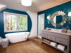 Custom designed architectural details frame the freestanding tub in this brilliant blue bathroom. Contractor Chip Wade of Elbow Room brings in a sisal area rug and jute rope accents to add a natural and beachy touch to this contemporary space.