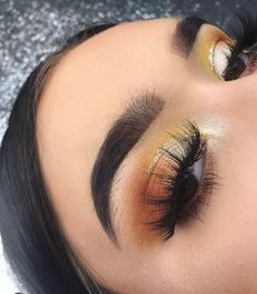 thick brows with orange and yellow eyeshadow, makeup for brown eyes.