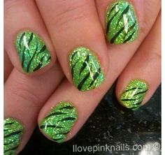 Green glitter nails with black tiger stripes