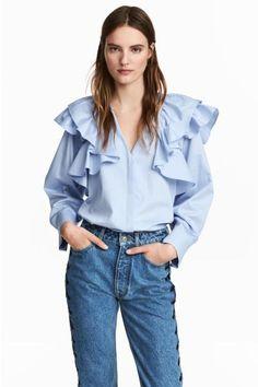 Een rechte blouse van geweven katoen met brede volants boven en lange, wijde mouwen met plooien en sluiting onderaan. De blouse heeft een V-hals en een blin