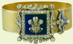 Queen Alexandra's Gold Bracelet with a Diamond and Enamel Buckle. This circa 1830 bracelet was a wedding present to Princess Alexandra of Denmark from the Duke of Cambridge, Queen Victoria's first cousin, and Alexandra's maternal/paternal 2nd cousin. The three diamond ostrich feathers in the center are the heraldic badge of the Prince of Wales. The enamel clasp appears to date from early in the reign of King William IV, the Duke's uncle.