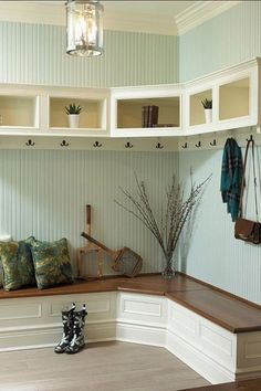 "Mud Room with Hardwood floors, Built-in bookshelf, Crown molding, Pental sign porcelain tile in cream battiscopa 3x18"", Paint"