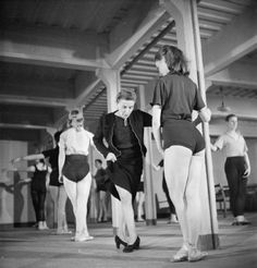 Marie Rambert (centre), founder and director of the Ballet Rambert, demonstrates a new step to ballet dancer Sally Gilmour, during a rehearsal in the games room of the factory hostel. This rehearsal is taking place in the morning, whilst the factory workers are busy at their jobs.