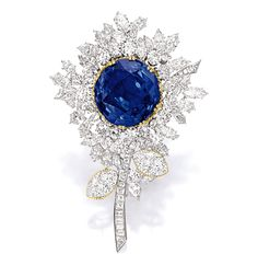 SAPPHIRE AND DIAMOND 'FLOWER' BROOCH Designed as a flower, centring on a circular-cut sapphire weighing 43.43 carats, the petals and stems set with marquise-shaped, brilliant-cut and baguette diamonds together weighing approximately 13.00 carats, the leaves set with two marquise-shaped diamonds weighing 2.01 and 2.00 carats respectively, mounted in 18 karat white and yellow gold.