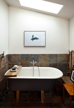 Mini House: Just look at that beautiful skylight above the tub! I suppose if it ever sprang a leak--it really wouldn't destroy anything b/c it would drip into the tub. Really like how bright this room is even with the dark wood and tile.