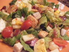torn salad greens  large tomatoes, chopped  1 1/2 pounds boneless skinless chicken breasts, cooked and cubed  5 bacon strips, cooked and crumbled   •2 hard-cooked eggs, sliced •1 cup of chunked Mozzarella Cheese  •1 cup of Red Onion