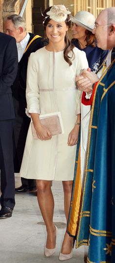 10-23-2013 - Middleton attended the christening of her royal nephew Prince George at St James's Palace in London wearing an ivory coatdress, floral fascinator, and matching accessories.