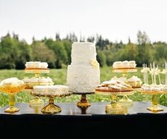 This yellow dessert table, covered in white sweets, is perfect for a outdoor country wedding.