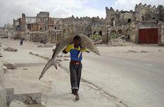 Un uomo traporta a spalle un grosso squalo per le strade di Mogadishu, in Somalia. foto: © Omar Feisal, Somalia, for Reuters