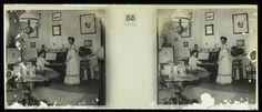 anoniem | Lize Brouwers naast de piano in een huis in Paramaribo, possibly Theodoor Brouwers, 1913 - 1930 | Interieur met Lize Brouwers staande naast de piano in een huis in Paramaribo, een vriendin zit achter de piano.