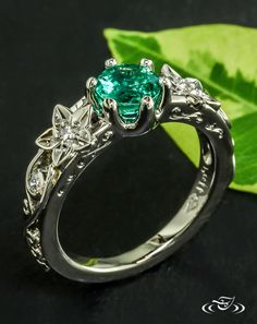 Emerald Floral Engagement RingA round emerald blooms from a 6 prong palladium setting surrounded by cast flowers and twisting vine filagree. #Ido #GreenLakeMade #EngagementRing