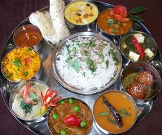 Thali - a large plate with various Indian food. With 22,464 delicacies from the states of Gujarat and Rajasthan alone, the possibilities of Indian food are endless. This is typical food eaten for lunch or dinner in India.  It could consist of 4 types of shaak/subji made with potatoes, okra, beans, chickpeas etc, raita - indian yogurt, pickles, lentils, vegetables, paratha (flaked indian bread), Daal (spicy indian lentil soup), a Indian sweet (mithai) and is one of the most healthiest meals