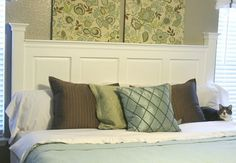 Headboard made from old door, trimmed out with side posts, post caps and crown moulding.
