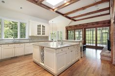 Traditional Kitchen with High ceiling, flush light, L-shaped, Flat panel cabinets, Limestone Tile, Skylight, Hardwood floors