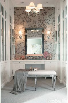 Dressing room and closet by Mary McDonald grey and cream floral wallpaper, upholstered mirror bench white cabinets and drawers