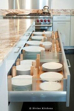 Instead of storing plates in upper cabinets, this kitchen from Divine Kitchens uses plate drawers with adjustable dividers More