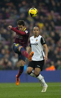 El defensa del FC Barcelona Jordi Alba despeja un balón ante el balón ante el centrocampista argelino del Valencia Sofiane Feghouli