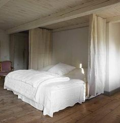 Curtains on either side of a bed add a sense of enclosure when a room is too large.