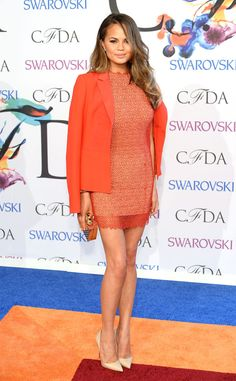 Supermodel Chrissy Teigen drapes a bright orange blazer over her matching lace mini dress.