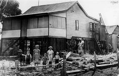 Kuhler family home at Carindale (known as Belmont then), Brisbane, 1940 - Five children stand in front of a wooden home on the corner of Scrub Road and Old Cleveland Road. This area was formerly Belmont.  A woman holds a young baby and a man is painting the weatherboard timber home