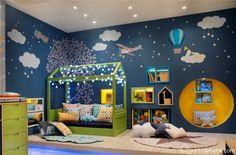 Quarto de bebê com berço iluminado com papel de parede azul com aviões e tapete com estrela