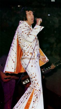 Elvis onstage in 1973. Unknown location. This jumpsuit was called the Orange Sunburst jumpsuit, and had a matching cape. It was seen on the album Raised On Rock.