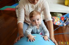 Uma bola de exercício e 5 brincadeiras fantásticas para seu bebê - bebê em pé apoiada na bola