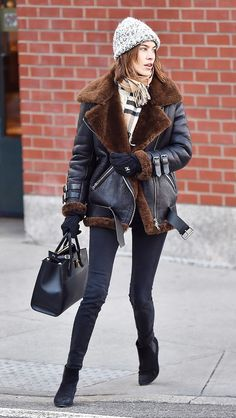 Alexa Chung wears a shearling moto jacket, Burberry scarf, grey knit beanie, black skinny jeans, and booties