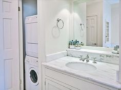 Washer and dryer tucked in corner closet in bathroom