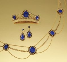 GOLD, ENAMEL, SEED PEARL AND LAPIS LAZULI PARURE, CIRCA 1810.  Comprising: a necklace, designed as a series of graduated medallions, each centring on an oval cabochon lapis lazuli within open work surrounds of seed pearls and blue enamel, connected by loop-in-loop and stylised foliate chains; accompanied by a pair of ear pendants of similar design and a comb centring on three oval cabochon lapis lazuli embellished with cannetille decoration