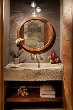 The rustic features of this Vail, Colorado, powder room, such as the cement sink and wood mirror, are balanced by the contemporary pendant lights.