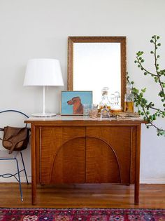 """17 Stylish Boho-Chic Designs by Emily Henderson for HGTV: """"A great mix of styles in this vignette is grounded with natural elements and a bright color scheme. A vintage console acts as storage and a bar and is made less serious with a whimsical flea market dog portrait and a modern white metal lamp. The branch leaning in acts like an organic sculpture and brings life into this vignette."""""""