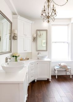 white bathroom with white wall and ceiling, white vanity, chandelier, wooden flooring, mirror, sconces of Longer Vanity with L Shaped Vanity in the Bathroom