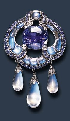 A RARE SAPPHIRE AND MOONSTONE BROOCH, BY LOUIS COMFORT TIFFANY, TIFFANY & CO. Centering upon a cushion-cut sapphire, within a scrolling frame of calibré-cut moonstones, to the slightly graduated circular-cut sapphire swag trim, suspending three drop-shaped moonstone terminals with platinum filigree caps, enhanced by spiral platinum filigree detail, mounted in platinum and gold, circa 1910-1915, in its original Tiffany & Co. black leather fitted case Signed Tiffany & Co.